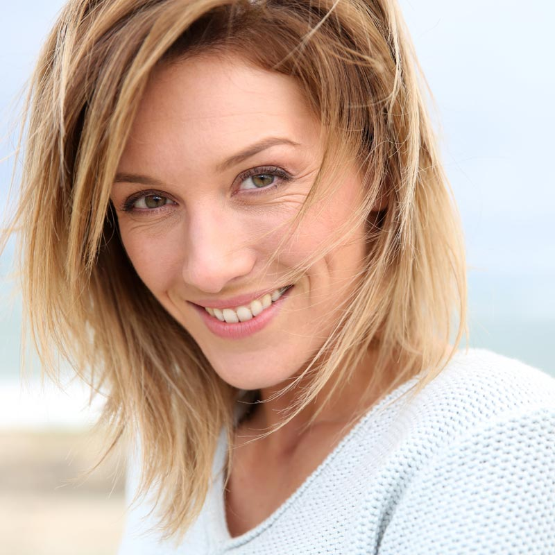 White Middle Aged Lady with Brownish Hair with Blonde Highlights Wearing a White V-Neck Sweater